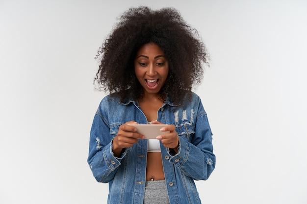 Blij mooie jonge donkere gevilde vrouw in witte top en jeans jas poseren over witte muur met mobiele telefoon in handen, scherm kijken en bericht typen met opgewonden gezicht