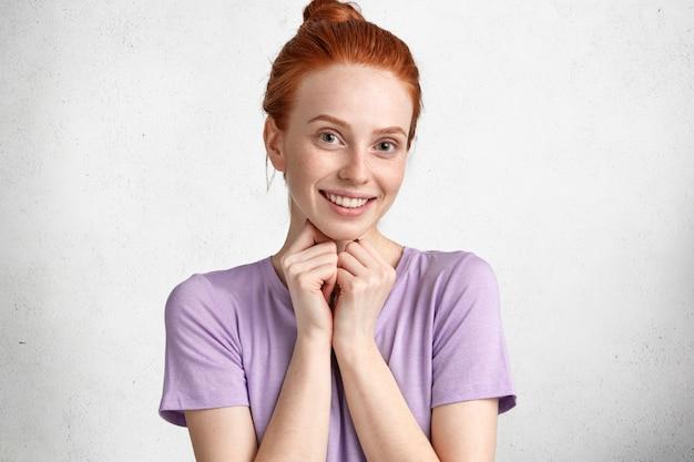 Blij mooie jonge vrouw met sproeten met positieve uitdrukking, glimlacht vreugdevol, blij om voorstel van vriend te ontvangen, gekleed in casual t-shirt