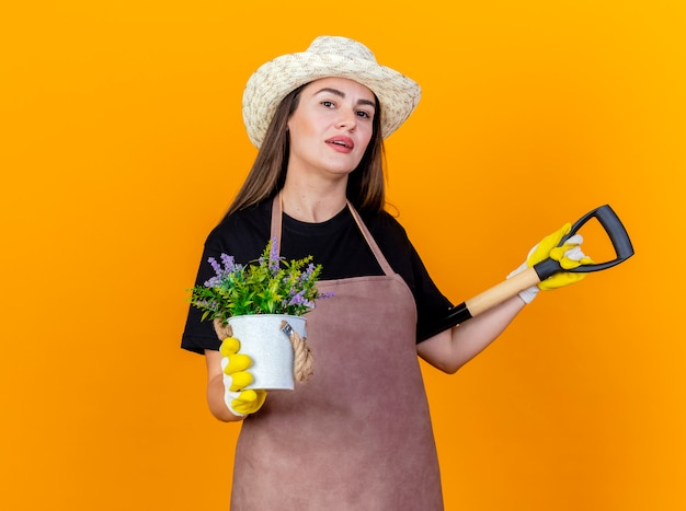 Blij mooie tuinman meisje uniform dragen en tuinieren hoed met handschoenen schop zetten schouder en houden bloem in bloempot geïsoleerd op een oranje achtergrond
