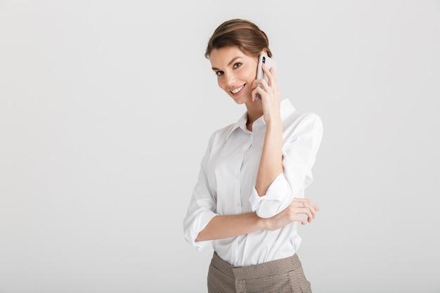 Blij mooie vrouw glimlachend en praten op mobiele telefoon geïsoleerd op wit