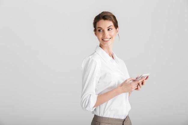 Blij mooie vrouw glimlachend en typen op mobiele telefoon geïsoleerd op wit