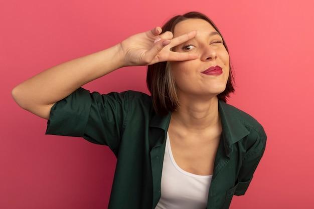 Blij mooie vrouw knippert oog en gebaren overwinning handteken naar voren kijken door vingers geïsoleerd op roze muur
