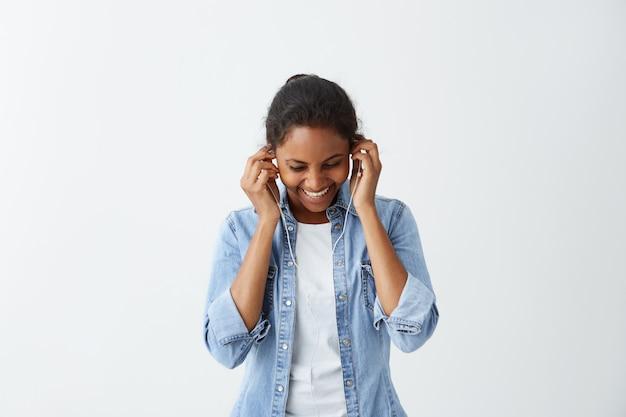 Blij mooie vrouw met haar knot, donkere ogen en gezonde donkere huid gekleed in wit t-shirt, blauwe jas, oortelefoon op, glimlachend terwijl poseren tegen witte betonnen muur. mensen en levensstijl.