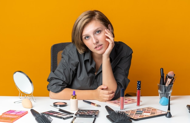 Blij mooie vrouw zit aan tafel met make-up tools hand op de wang zetten