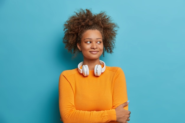 Blij mooie vrouwelijke tiener met krullend haar houdt handen gekruist over borst draagt koptelefoon over nek en kijkt gelukkig opzij.