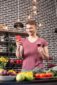 Blij na bericht. blondharige vriend voelt zich gelukkig na het lezen van een bericht van een vriendin na het koken van het avondeten