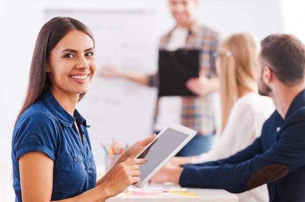 Blij om deel uit te maken van een team. zelfverzekerde jonge vrouw die een digitale tablet vasthoudt en glimlacht terwijl de man op de achtergrond staat en naar het whiteboard wijst