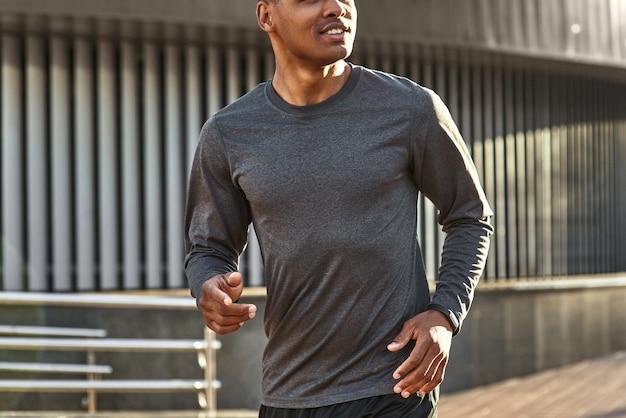 Blij om een gezond close-upportret te zijn van een knappe en positieve afrikaanse man in sportkleding die begint