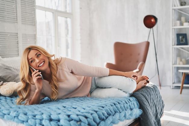 Blij om met vriend te praten. aantrekkelijke jonge vrouw die op haar smartphone praat en glimlacht terwijl ze thuis op bed ligt