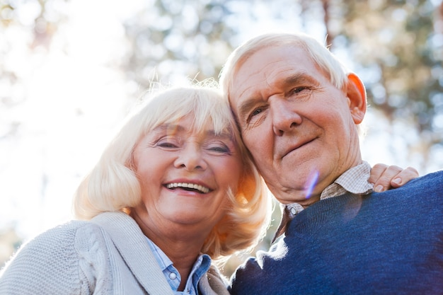 Blij om samen te zijn. lage hoekmening van gelukkig senior koppel dat zich aan elkaar hecht en glimlacht terwijl ze buiten staan