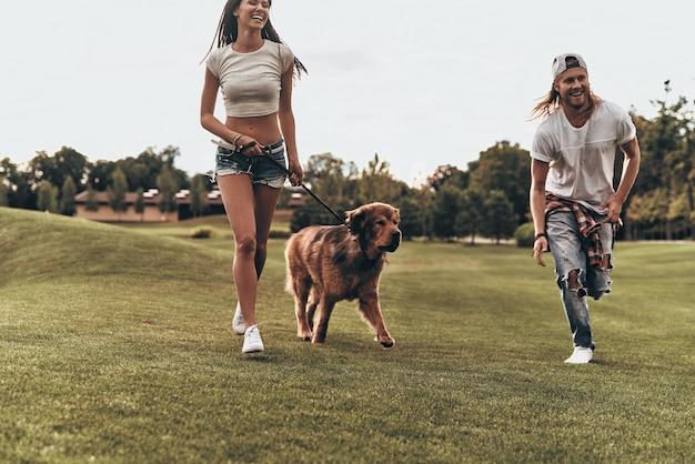Blij om samen te zijn. volledige lengte van een mooi jong stel dat met hun hond speelt tijdens het rennen in het park