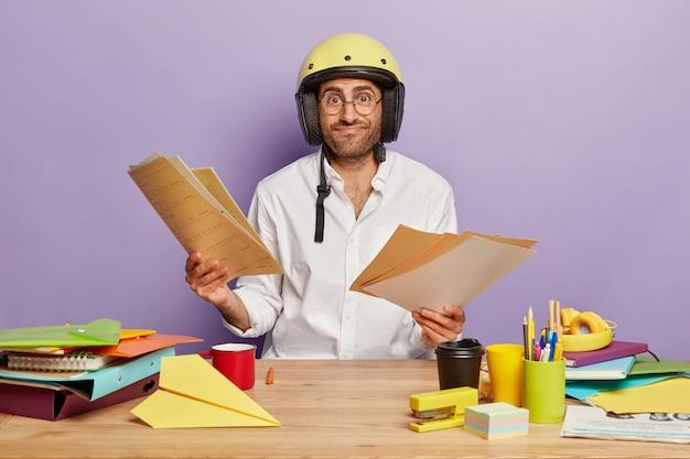 Blij ongeschoren man draagt helm en wit overhemd, kijkt door documenten op de werkplek, maakt project