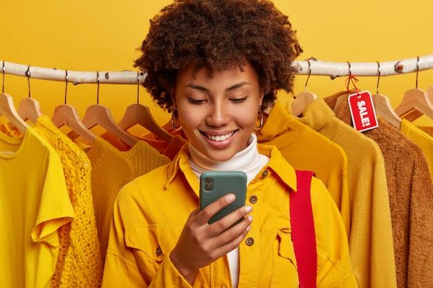 Blij online handelaar gericht op smartphoneapparaat, staat tegen gele kleding op rekken