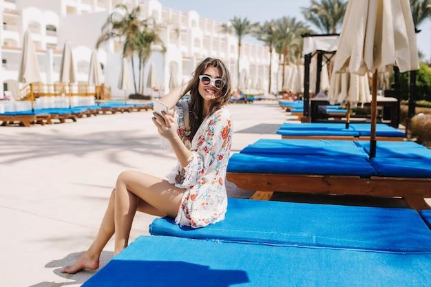 Blij op blote voeten mooi meisje dat op blauwe chaise-longue rust en met palmbomen glimlacht. portret van vrolijke jonge brunette vrouw zittend op schraag-bed met telefoon