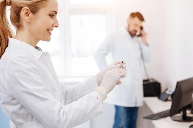 Blij opgetogen vrouwelijke arts die een spuit vasthoudt en glimlacht tijdens het voorbereiden van een injectie