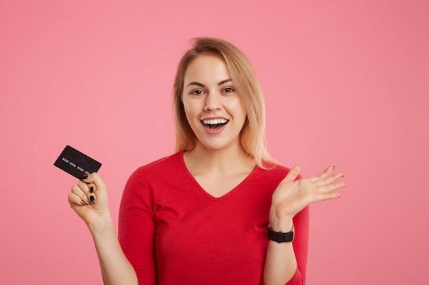 Blij opgewonden blonde vrouw houdt plastic kaart vast, verwacht geen salaris te ontvangen, gaat betalingen doen, kijkt vrolijk naar de camera