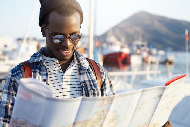 Blij opgewonden donkere man reiziger draagt stijlvolle kleding met stadsgids in zijn handen terwijl hij nadenkt waar te gaan, zee, bergen en jachten