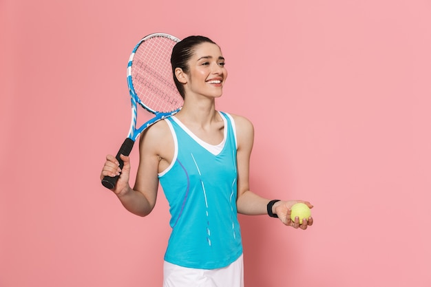 Blij opgewonden geweldige mooie jonge mooie fitness vrouw met tennisracket poseren geïsoleerd over roze muur