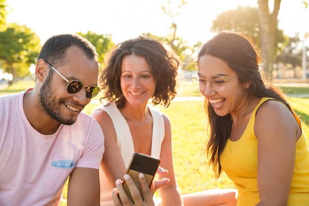 Blij opgewonden groep vrienden kijken naar video op de telefoon