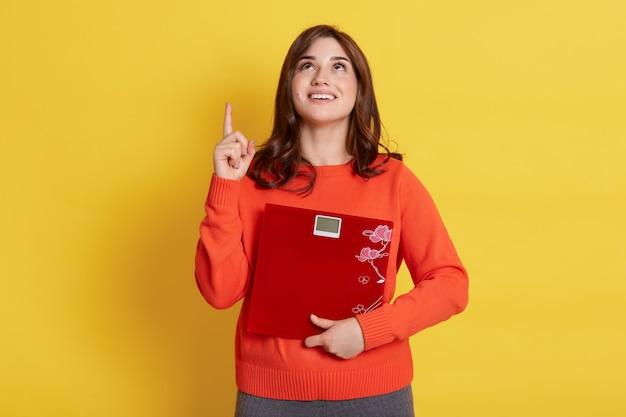 Blij opgewonden jonge donkerharige vrouw die rode vloerschalen omhelst, kijkt en omhoog wijst met wijsvinger, geïsoleerd over gele muur.
