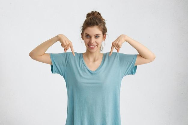 Blij opgewonden jonge vrouw grijnzend breed, trekt uw aandacht naar haar lege t-shirt, wijzende vingers