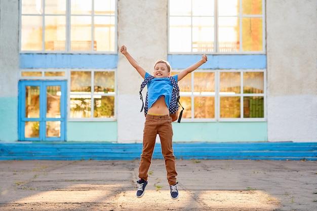 Blij opgewonden schooljongen is blij met het einde van het schooljaar, om vakantie te beginnen.