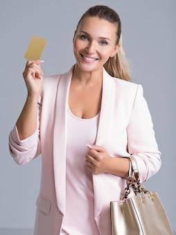 Blij opgewonden verrast jonge vrouw met creditcard over wit