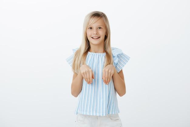 Blij opgewonden vrouwelijk kindje met blond haar in trendy blauwe blouse met handpalmen over de borst alsof het konijnenpoten zijn, breed glimlachend, zich verbaasd voelen tijdens het spelen met de rest van de kinderen op de speelplaats