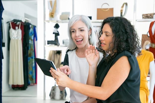 Blij opgewonden vrouwelijke shoppers die samen zitten en tablet gebruiken, kleren en aankopen in modewinkel bespreken. kopieer ruimte. consumentisme of winkelconcept