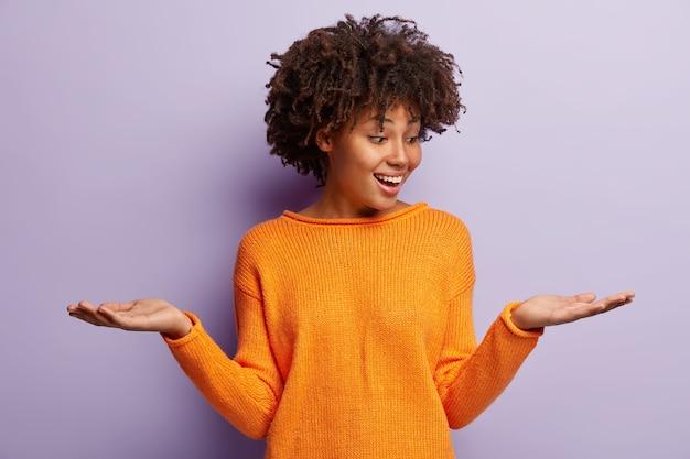 Blij, optimistische afro-amerikaanse vrouw steekt beide handpalmen op, doet alsof ze twee items vasthoudt, in een goed humeur is, draagt een casual outfit, geïsoleerd over een paarse muur. het tevreden wijfje houdt exemplaarruimte