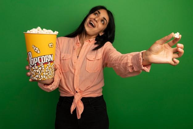 Blij opzoeken jong mooi meisje dragen roze t-shirt houden emmer popcorn geïsoleerd op groen
