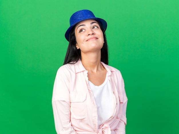 Blij opzoeken van jonge mooie vrouw met feestmuts geïsoleerd op groene muur