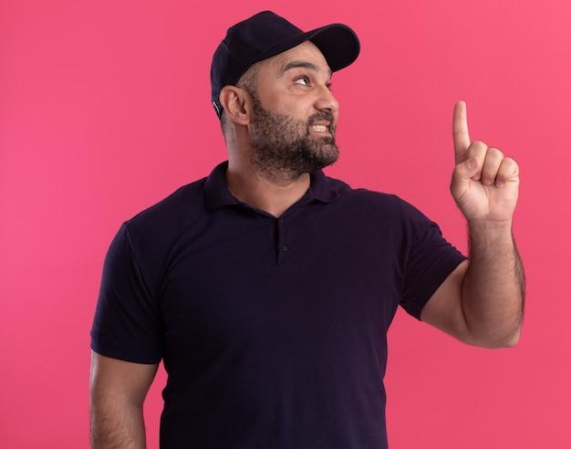 Blij opzoeken van middelbare leeftijd bezorger in uniform en pet wijst naar omhoog geïsoleerd op roze muur