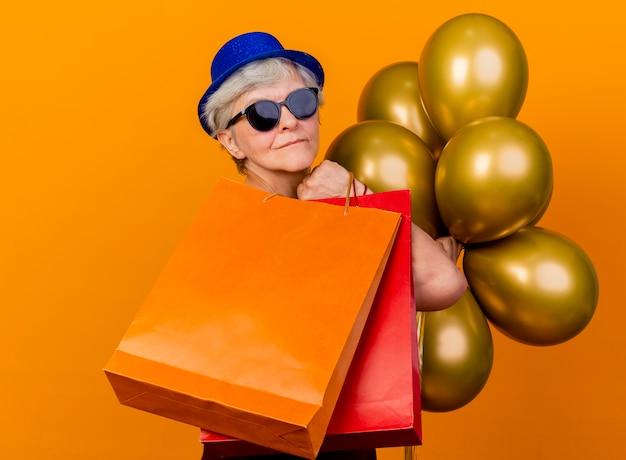 Blij oudere vrouw in zonnebril met feestmuts staat zijwaarts met helium ballonnen en papieren boodschappentassen geïsoleerd op een oranje muur met kopie ruimte