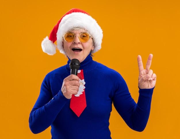 Blij oudere vrouw in zonnebril met kerstmuts en kerststropdas houdt microfoon die doet alsof ze zingt en gebaren overwinningsteken geïsoleerd op oranje muur met kopie ruimte