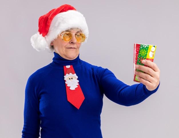 Blij oudere vrouw in zonnebril met kerstmuts en santa stropdas houden en kijken naar papieren beker geïsoleerd op een witte muur met kopie ruimte