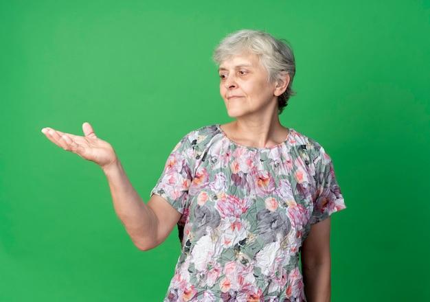 Blij oudere vrouw kijkt naar lege hand geïsoleerd op groene muur