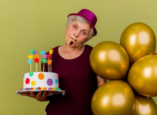 Blij oudere vrouw met feestmuts staat met helium ballonnen met verjaardagstaart blazen fluitje geïsoleerd op olijfgroene muur met kopie ruimte