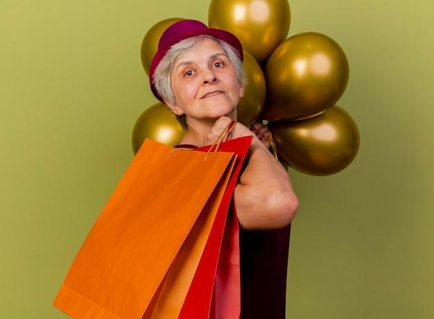 Blij oudere vrouw met feestmuts staat zijwaarts met helium ballonnen met papieren boodschappentassen geïsoleerd op olijfgroene muur met kopie ruimte