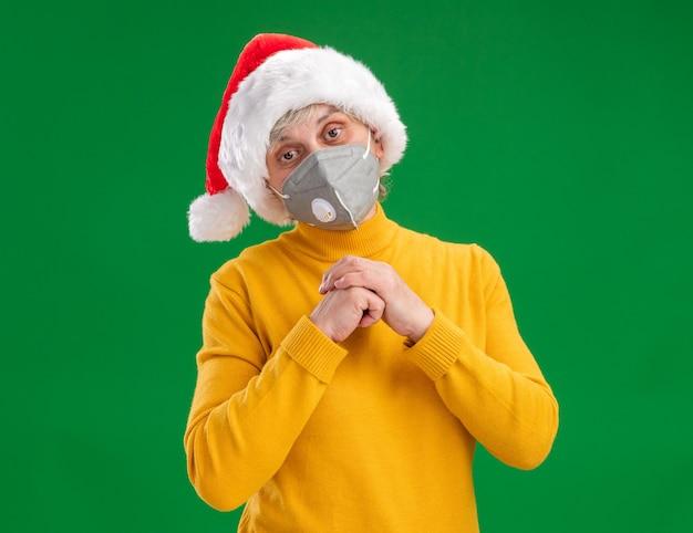 Blij oudere vrouw met kerstmuts dragen medische masker hand in hand samen kijken naar camera geïsoleerd op groene achtergrond met kopie ruimte