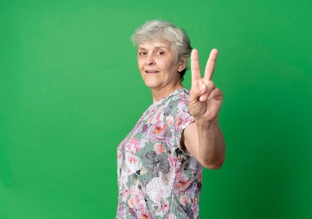 Blij oudere vrouw staat zijwaarts gebaren overwinning handteken geïsoleerd op groene muur
