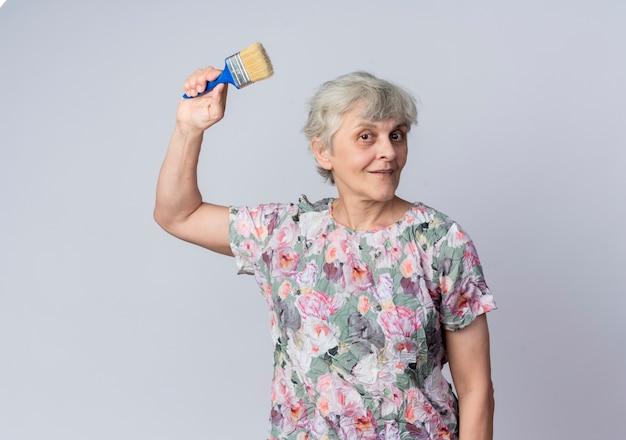 Blij oudere vrouw steekt hand omhoog met verfborstel geïsoleerd op een witte muur