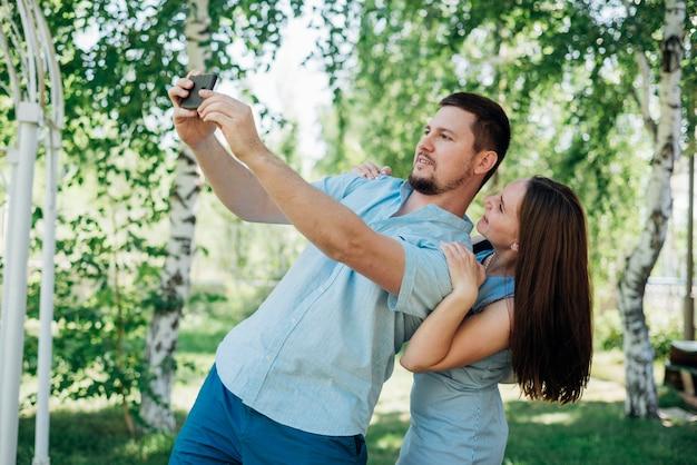 Blij paar die selfie in berkbos nemen