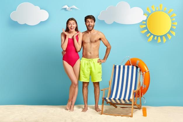 Blij paar poseren op zandstrand in het weekend. gelukkig man omhelst vriendin, heeft naakte torso, chillen op badplaats, lege zonnestoel