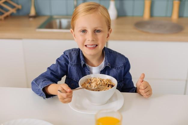 Blij positief jong meisje dat en duimen omhoog gebaar glimlacht toont terwijl het eten van een gezond smakelijk ontbijt
