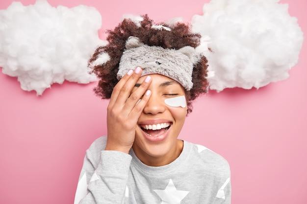Blij positief meisje bedekt gezicht sluit ogen en glimlacht graag goedemorgen draagt nachtkleding geïsoleerd over roze muur witte wolken boven het hoofd