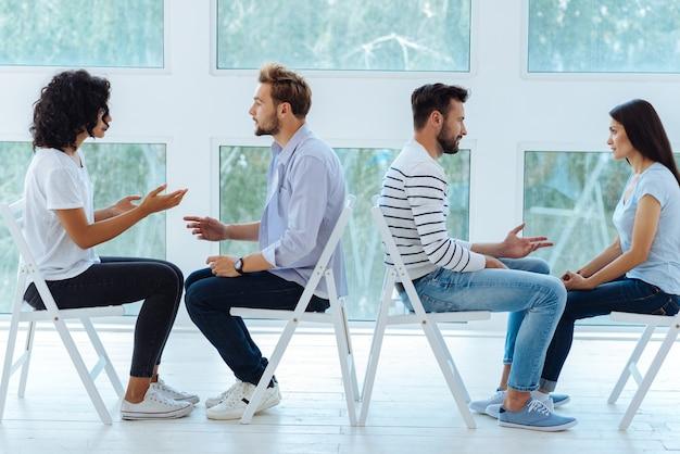 Blij positief opgetogen stel dat naar elkaar praat en naar elkaar luistert terwijl ze een psychologische activiteit doen