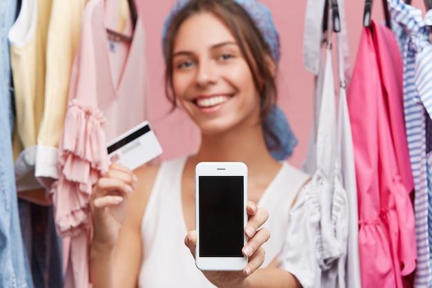 Blij positief wijfje dat zich dichtbij rek met kleren bevindt, mobiele telefoon en creditcard toont terwijl thuis online het winkelen doet gebruikend vrij internet. vrouwelijke koper met gelukkige blik verheugende aankoop