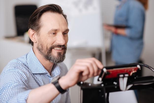 Blij positieve bebaarde man kijken naar de 3d-printer en het controleren van instellingen tijdens de voorbereiding om te beginnen met afdrukken