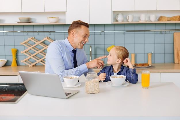 Blij positieve gelukkige man kijkt naar zijn dochter en raakt haar neus aan